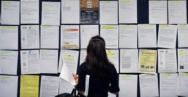 A woman looks over the job postings at the One-Stop Center in Irvine. The center offers free services for people in search of a job. (Mark Rightmire,/ZUMA Press/Newscom)