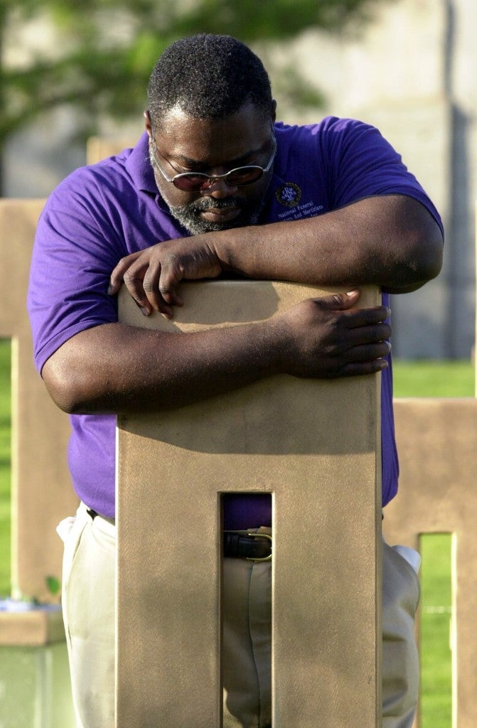 Jimmie Boldien hugs the chair of his aunt, Laura Jane Garrison, at the Oklahoma City National Memorial on Monday, June 11, 2001.  (Photo: Vert/Newscom)