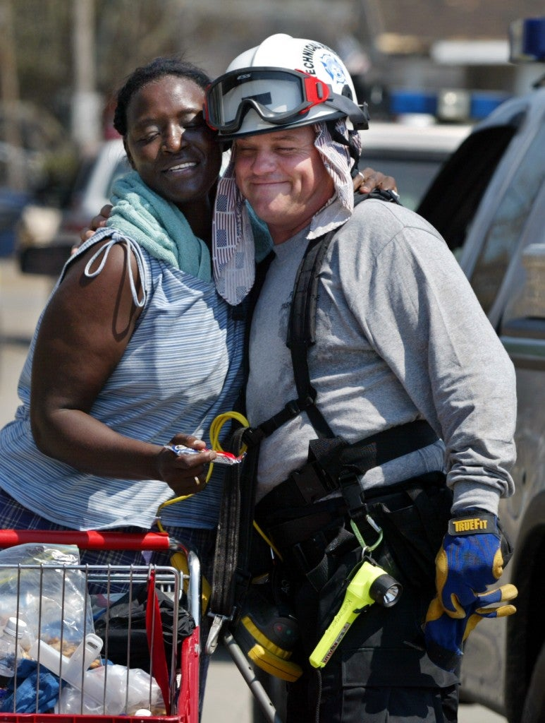 """God bless you babies,"" Anita Averhart said to Stan Kordecki, of St. Petersburg Fire Rescue, as firefighters searched for Hurricane Katrina survivors and bodies. (Photo: Jared Lazarus/KRT/Newscom)"