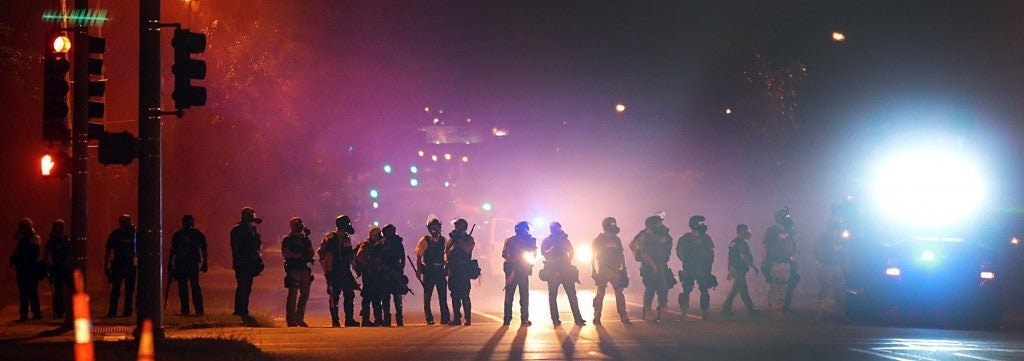 Tactical officers work their way north on West Florissant Avenue in Ferguson, Mo., clearing the road of residents, on Wednesday, Aug. 13, 2014. (Photo: Robert Cohen/St. Louis Post-Dispatch/MCT)
