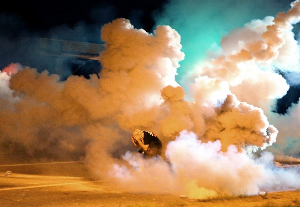 During the fourth night of unrest, a rotester takes shelter from the tear gas exploding around him. (Photo: David Carson/St. Louis Post-Dispatch/MCT)