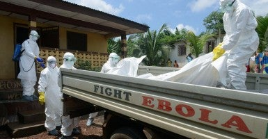 Liberian Red Cross staff carry the body of a patient who died after being infected with the Ebola virus onto a truck on Sept. 4, 2014, in Monrovia, Liberia. (Photo: Tomoaki Nakano/Newscom)