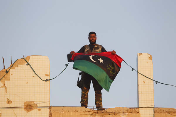 A Libyan rebel holds a Kingdom of Libya flag at Bab Al-Aziziya compound in Tripoli August 23, 2011.