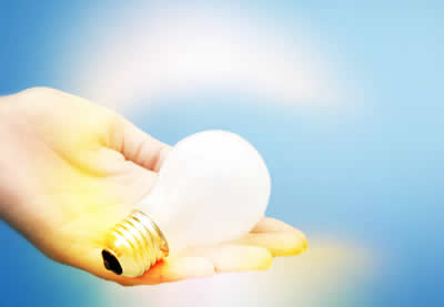 Light bulb glowing in hand