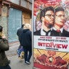 Pedestrians walk past an advertisement for 'The Interview,' a comedic film about North Korean leader Kim Jong-Un's assassinat
