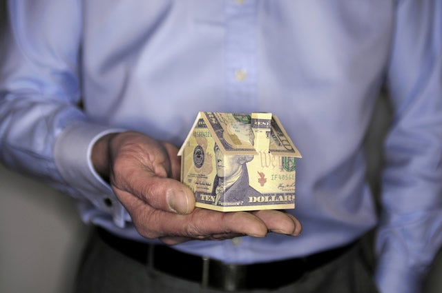 man-holding-home-folded-cash