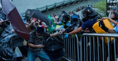 Protesters are pepper sprayed by police but hold their ground protected by rain coats, goggles and umbrellas. (Photo: Todd Darling/Polaris/Newscom)