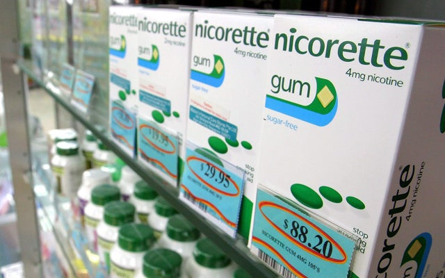 Singapore pharmicist stands near chewing gum for sale in Singapore