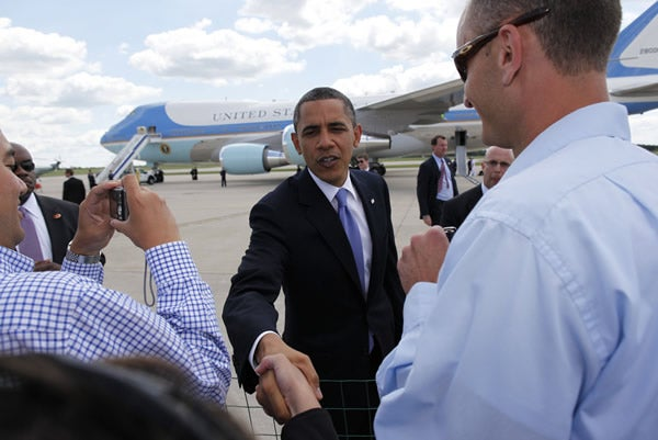 U.S. President Barack Obama shakes hands after he arrives at Gerald Ford International Airport in Grand Rapids, Michigan
