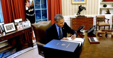 President Barack Obama signing the Consolidated Appropriations Act in the Oval Office on Dec. 18, 2015. (Photo: Olivier Douliery Pool /CNP/Newscom)