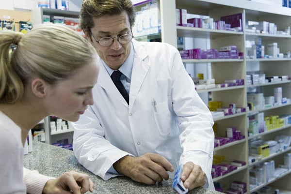 pharmacist consults with young woman