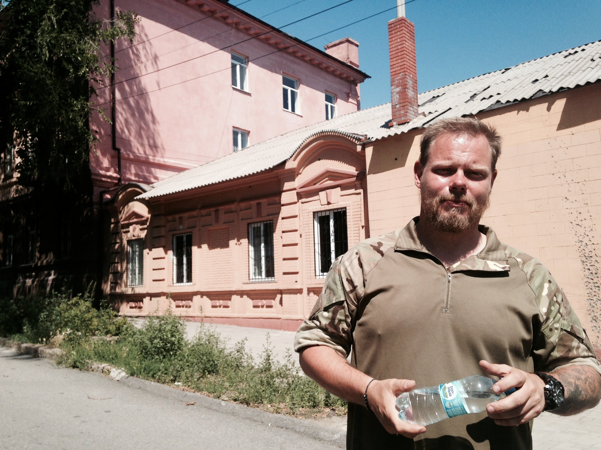 Skillt in Mariupol at the scene of his first battle. The school house and third-floor window are in the background. (Photo: Nolan Peterson/The Daily Signal)