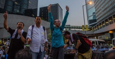 Jimmy Lai (second from left), founder of Next Media, addresses pro-democracy demonstrators immediately after police released  tear gas outside government headquarters. (Photo: Todd Darling/Newscom)
