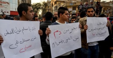 Egyptian youths hold placards during a demonstration to denounce the killing of Egyptian Christians in Libya. (Photo: Amr Sayed/Apaimages/Polaris)