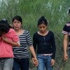 A group of Central American immigrants walks toward U.S. Border Patrol agents  to surre