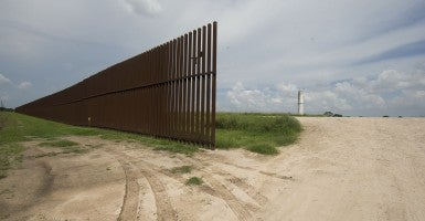 The border wall runs several miles through a rural area east of Brownsville. (Photo: Bob Daemmrich/Newscom)