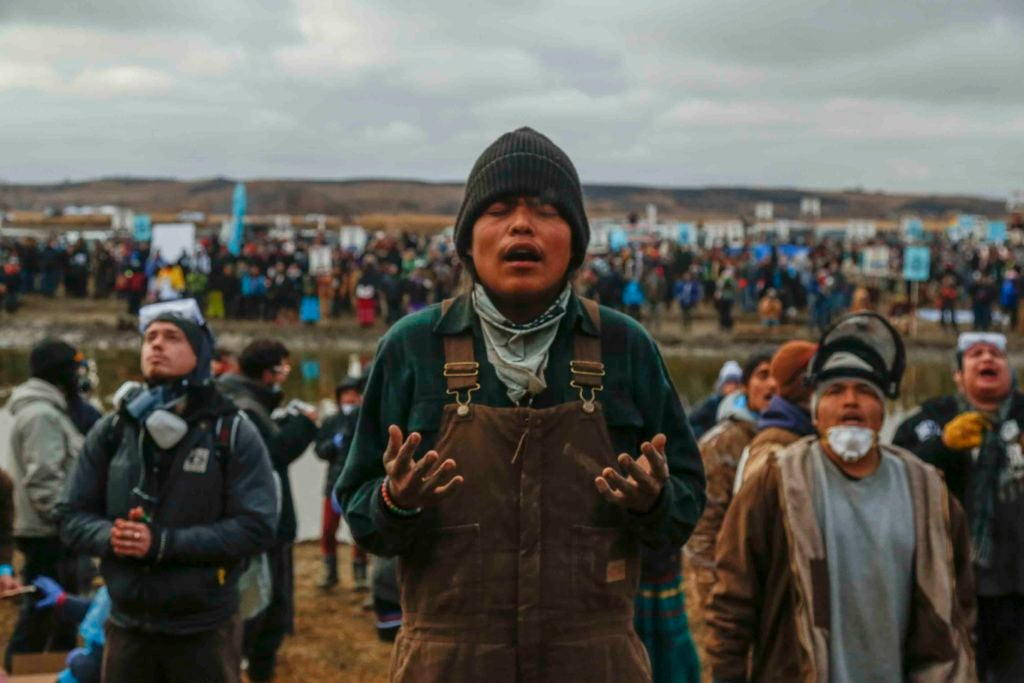 During a Nov. 23 protest against the Dakota Access pipeline, Frankie Tso Jr. prays amongst other demonstrators at the foot of a hill off the Missouri River surrounding the Standing Rock Indian Reservation. (Photo: Natasha Dangond/Polaris/Newscom)