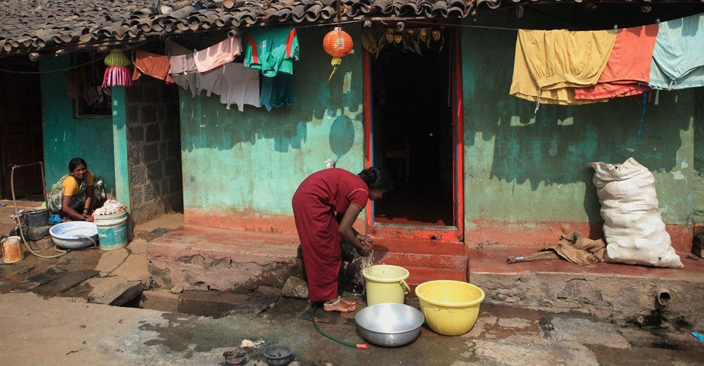 A slum woman in India washes clothes from the  tap  water in the Slum neighbourhood at Belgaum. [Photo via Newscom]