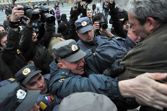 Police officers detain an anti-Putin protester at the central Dvortsovaya Square in Saint-Petersburg , on May 7, 2012.