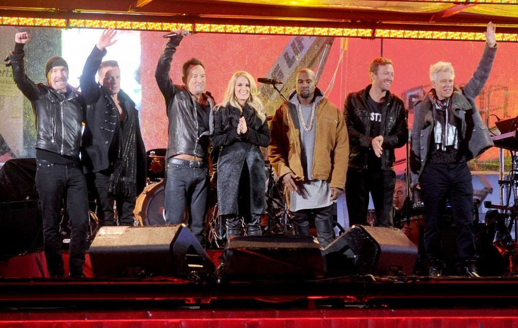 The Edge, Larry Mullen Jr, Bruce Springsteen, Carrie Underwood, Kanye West, Chris Martin and Adam Clayton at a Surprise World AIDS Day (Red) concert at Times Square on Dec. 1. (Photo: Newscom)