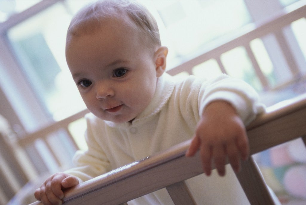 Close-up of a baby boy holding the railing of a crib