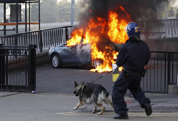 A policeman and his dog walk towards a burning car amid riots in central Birmingham, central England August 9, 2011.
