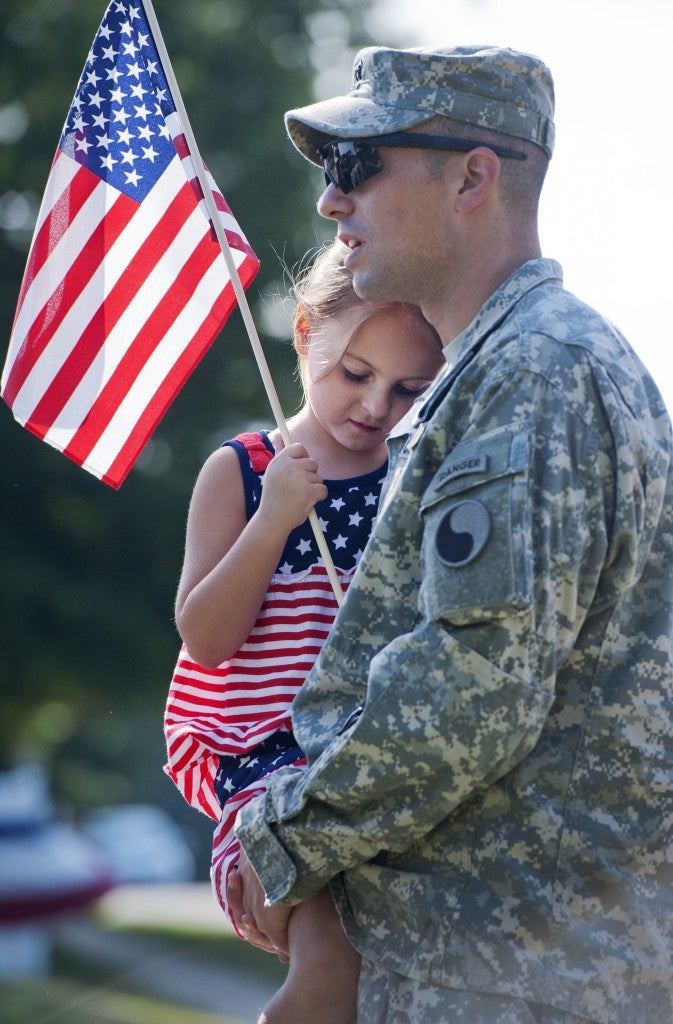 Capt. Brandon Price of the Virginia National Guard and his daughter Chloe, 5, prepare to march in Leesburg's Independence Day parade, 2014. (Photo By Tom Williams/CQ Roll Call/ Newscom)