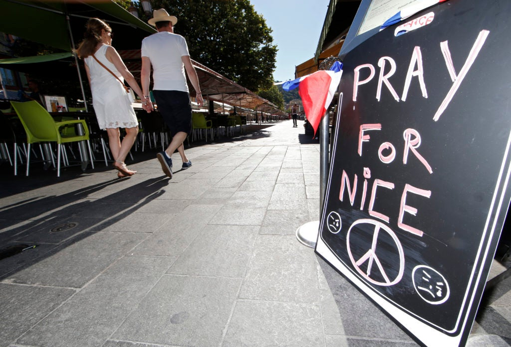 "A couple walk through the empty flower market in the old city and near a sign which reads, ""Pray for Nice"" days after a truck attack on the Promenade des Anglais on Bastille Day killed scores and injured as many in Nice, France, July 17. (Photo: ERIC GAILLARD/REUTERS/Newscom)"