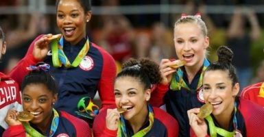 Simone Biles, Gabby Douglas, Laurie Hernandez, Madison Kocian, and Aly Raisman pose with their gold medals on the podium after winning the women's team final. (Photo: Mike Blake/Reuters/Newscom)