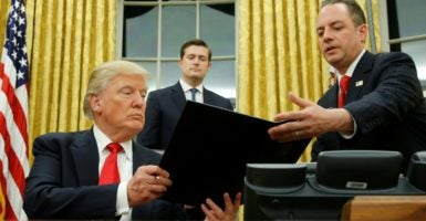 President Donald Trump hands Chief of Staff Reince Priebus an executive order that directs agencies to ease the burden of Obamacare. (Photo: Jonathn Ernst/Reuters/Newscom)