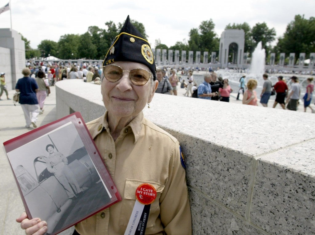 World War II veteran Anne Greenberg, 85, of Phoenix poses with a photo of herself from 1943, at the World War II Memorial in Washington May 28, 2004. (Photo: Yuri Gripas/Newscom)