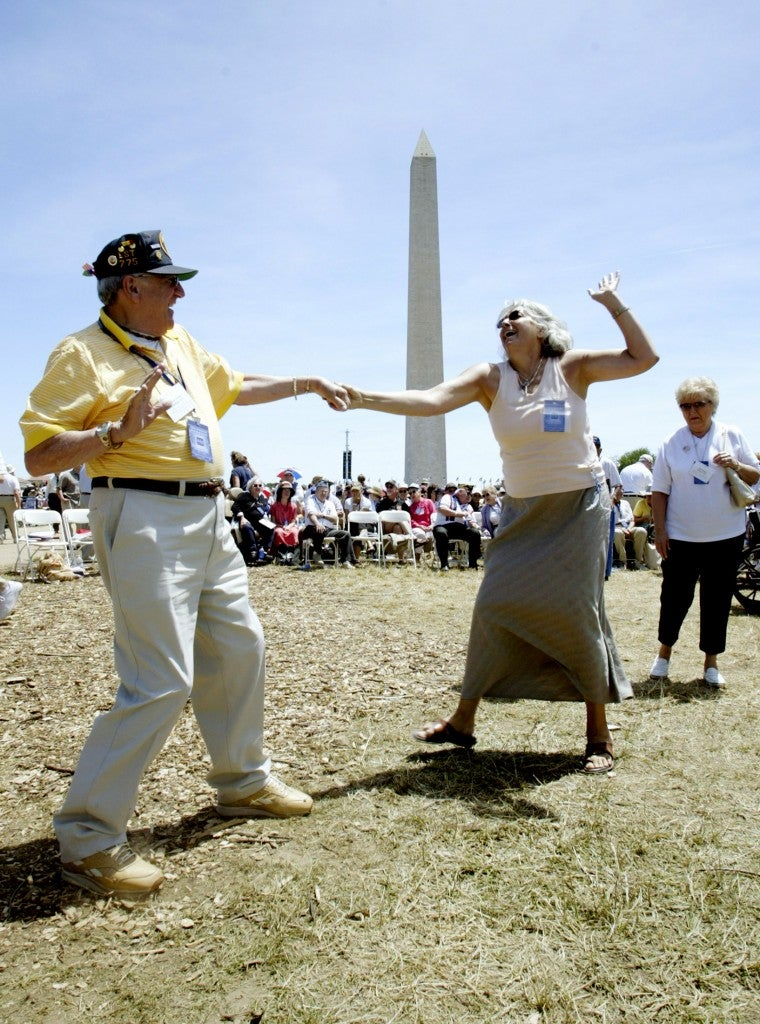Anthony Grasso (L) from Lynnfield, Massachusetts, a botswain mate who served on the USS LST-775 in the Pacific during World War Two, dances with Tanya Wohner before the dedication ceremony for the National WW II Memorial, in Washington, May 29, 2004. (Photo: John Pryke/Newscom)