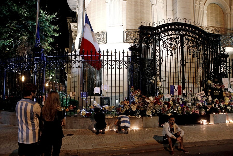 People light candles and stand outside the French embassy in Buenos Aires, Argentina. (Photo: REUTERS/Marcos Brindicci/Newscom)