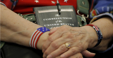 An audience member holds a copy of the U.S. Constitution during a Republican presidential debate in Des Moines, Iowa. (Photo: Brian Snyder/Reuters/Newscom)