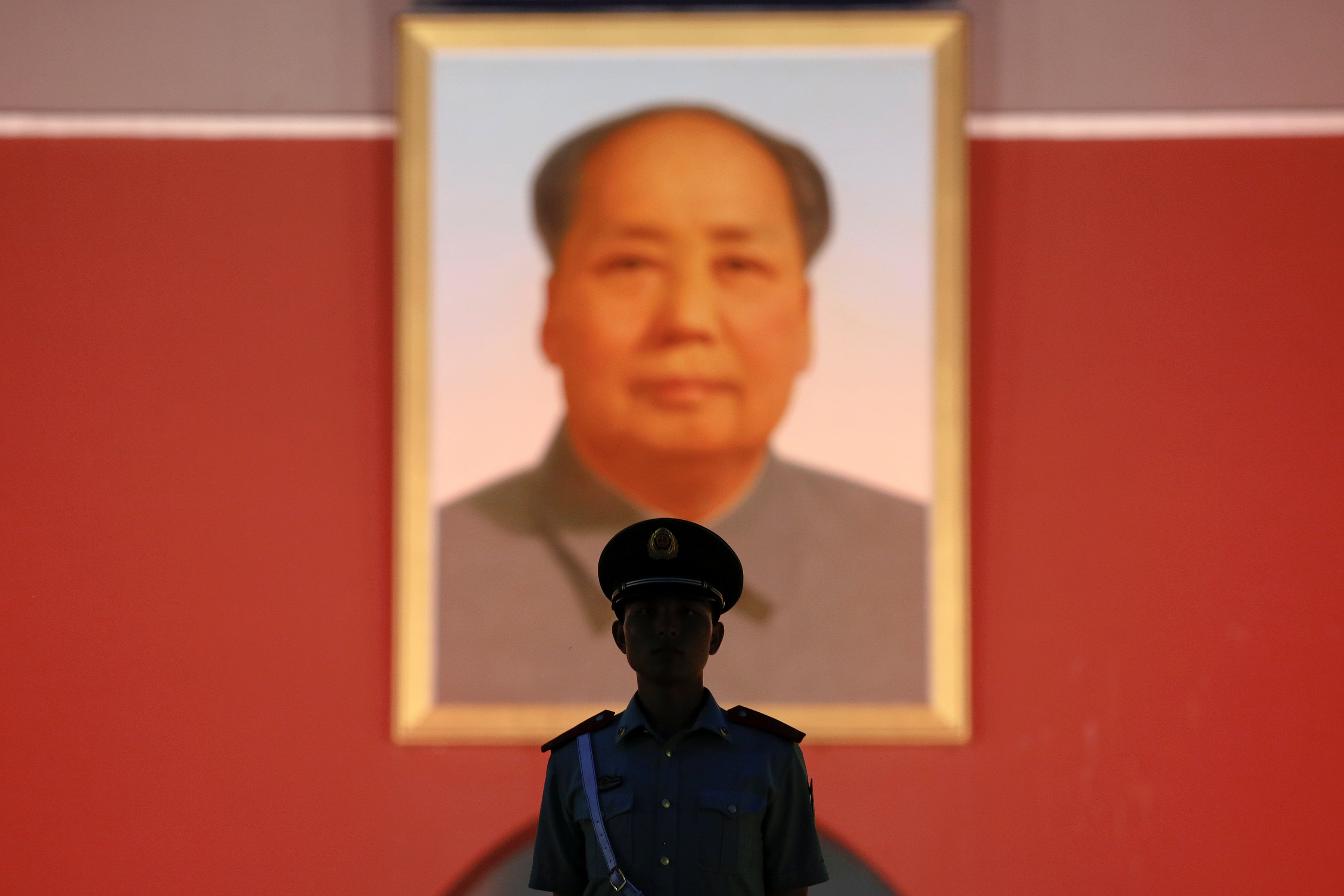 A paramilitary policeman stands guard under a giant for Chairman mao
