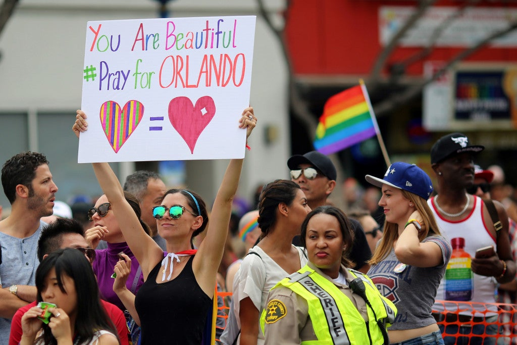 Kristen Jaeger holds a sign of remembrance for mass shooting victims in Orlando, at the Los Angeles Gay Pride Parade in West Hollywood, California. (Photo: David McNew/Reuters/Newscom)