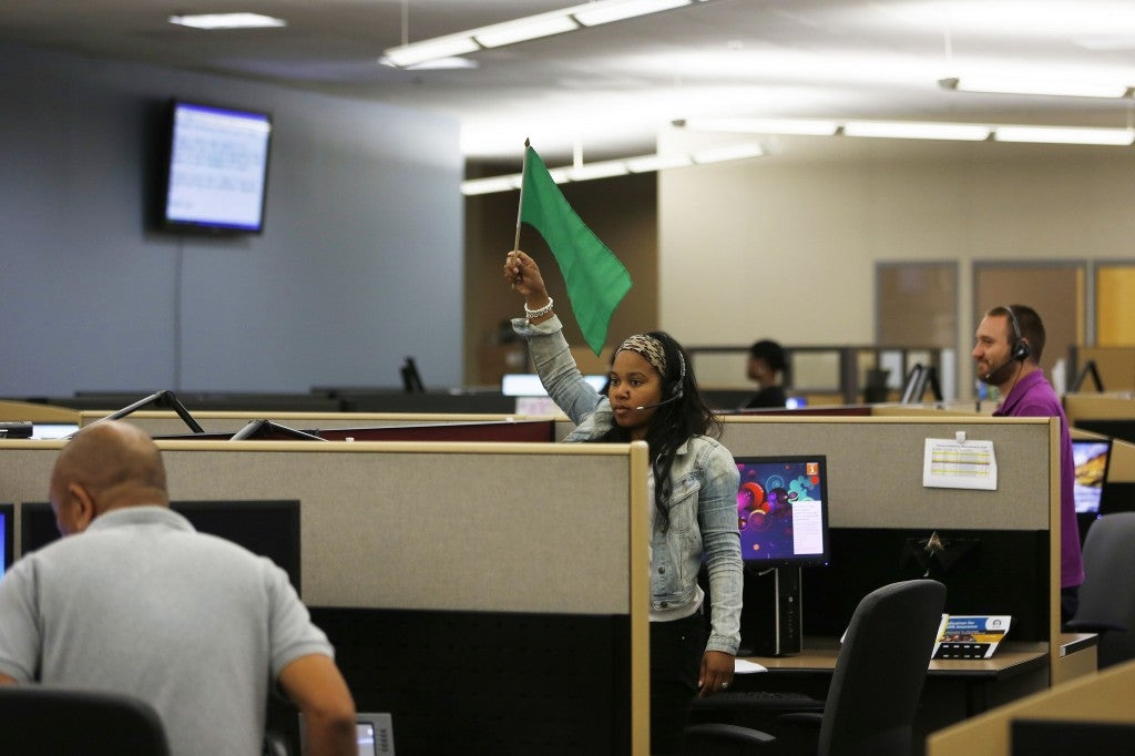A customer service agent at Covered California's Concord call center waves a flag for technical assistance during the opening day of enrollment of the Patient Protection and Affordable Care Act in Concord, California October 1, 2013. (Photo: Stephen Lam/Newscom)