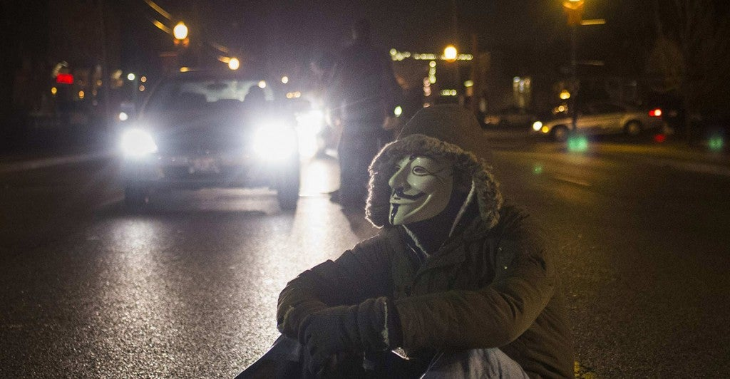 An activist, wearing a Guy Fawkes mask, blocks traffic while protesting outside the police station in Ferguson. (Photo: REUTERS/Adrees Latif/Newscom)