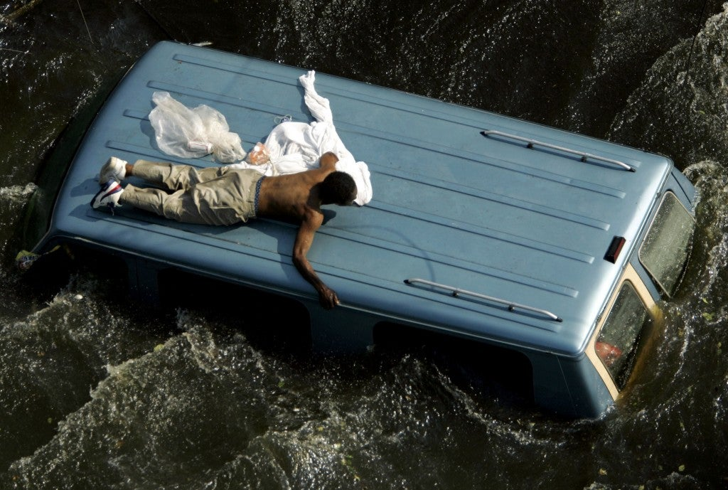 A man clings to the top of a vehicle before being rescued by the U.S. Coast Guard from the flooded streets of New Orleans, six days after the hurricane struck the city. (Photo: Robert Galbraith/Reuters/Newscom)