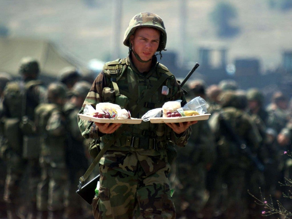 A U.S. marine carries food from a barbeque celebrating July 4 while on tour in Yugoslavia, 1999.    (Photo: Laszlo Balogh/ Reuters/Newscom)