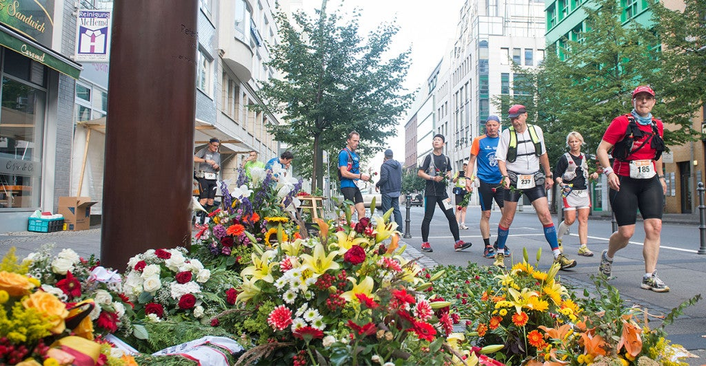 Participants in the Berlin 100 Miles run past the Checkpoint Charlie monument for Peter Fechter in Berlin, Germany. (Photo: Newscom)