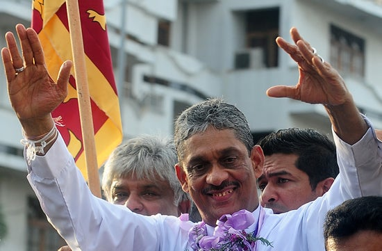 Sri Lanka's former army chief Sarath Fonseka gestures to supporters as he leaves the main prison in Colombo on May 21, 2012. AFP/GettyImages