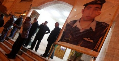 People stand by a poster of the Jordanian pilot Moaz al-Kasasbeh after the release of a video showing him being burnt alive in the pilot's hometown Karak, Jordan, on Feb. 3, 2015. (Photo: Mohammad Abu Ghosh/Newscom)
