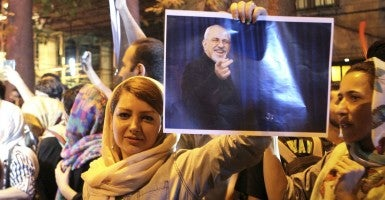 A woman holds a poster of Iranian Foreign Minister Mohammad-Javad Zarif to celebrate the nuclear agreement in Tehran. (Photo: Chine Nouvelle/SIPA/Newscom)