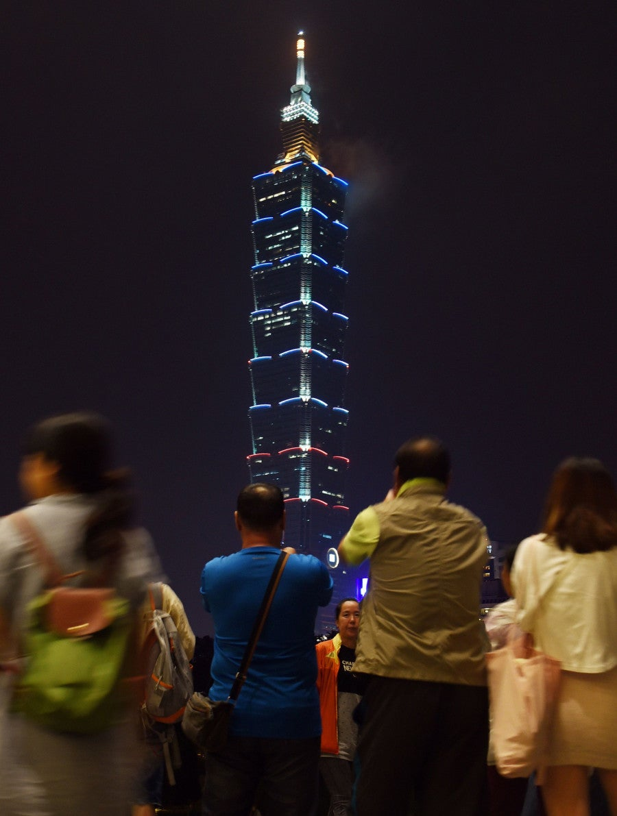 People watch the Taipei 101 building in Taipei, in southeast China Taiwan, light up with the colours of French national flag. (Photo: Xinhua/Wu Ching-teng/Newscom)