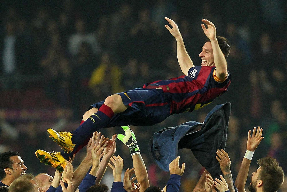 Lionel Messi of FC Barcelona is thrown into the air, at the end of the match by his teammates. (Photo: Giuliano Bevilacqua/Newscom)