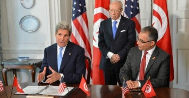 Secretary of State John Kerry signs Memorandum of Understanding with Tunisian Minister for Political Affairs Mohsen Marzouk while Tunisian President Beji Caid Essebsi looks on. (Photo: State Department/Sipa USA/Newscom)