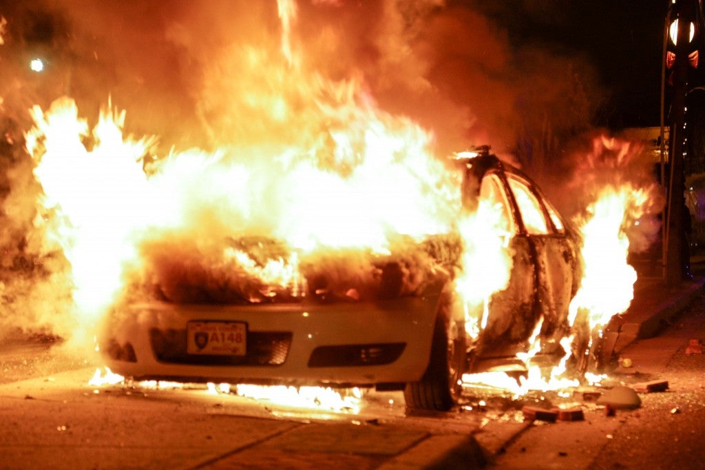 Angry protestors set police cars on fire in Ferguson. (Photo: Demotix/Newscom)