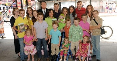 "The Duggar family visit the ""Today Show"" and pose for a group photo outside in Times Square. (Photo: Doug Meszler/Newscom)"