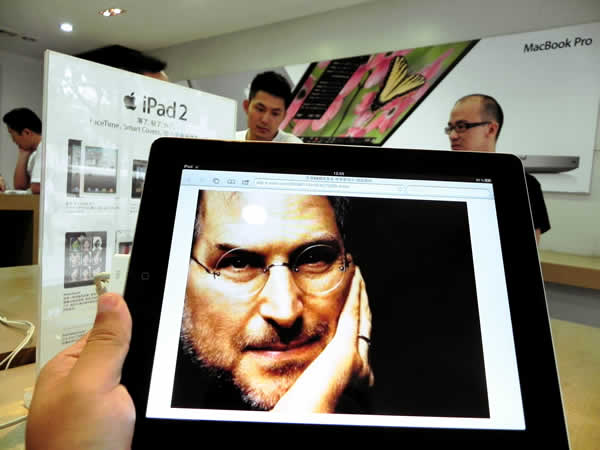 An iPad displays a picture of Apple CEO Steve Jobs